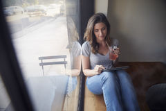 Young woman sits beside window in cafe using tablet computer Stock Photos
