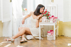 Young woman sits at a window and smells flowers. Young woman in a summer dress with gift boxes and roses Stock Photos