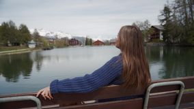 Young woman sits on a wooden bench with amazing view over lake and mountains and relaxed on sunny spring day. Woman. Enjoying a picturesque place. Rear view 4k stock footage