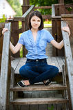 Young woman sits on wooden ladder Royalty Free Stock Photos
