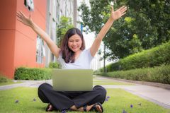 Young woman sits on the yard in the garden with laptop and raisi. Ng her hands like a winner in a game Royalty Free Stock Image