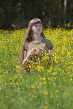Young woman sits among yellow flowers at meadow Stock Photography