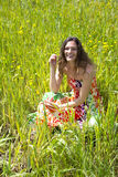 Young woman sitted in a field of flowers. Royalty Free Stock Photos