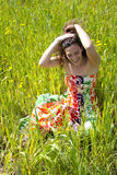 Young woman sitted in a field of flowers. Stock Images