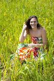 Young woman sitted in a field of flowers. Stock Photos