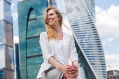 Young woman sitting against office buidings. Royalty Free Stock Images