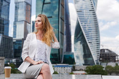 Young woman sitting against office buidings. Coffee break, lunch concept Royalty Free Stock Images