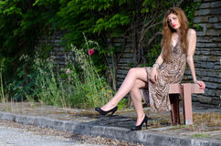 Young woman sitting against rocks wall with long leaves Royalty Free Stock Images