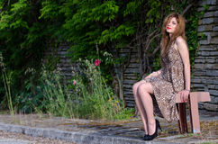 Young woman sitting against rocks wall with long leaves Royalty Free Stock Image