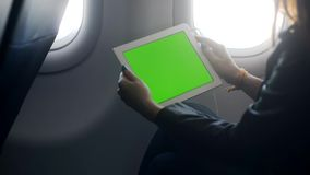 Young woman is sitting at aircraft and watching, listening media information from tablet. Modern student at first class with touchscreen technology on smart stock footage