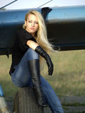 Young woman sitting on airplane landing gear Stock Photo