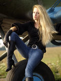 Young woman sitting on airplane landing gear Royalty Free Stock Photos