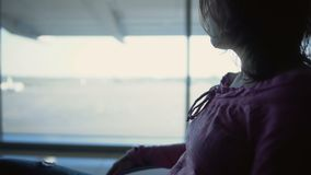 Young woman sitting in airport terminal, waiting for flight, meeting relatives. Stock footage stock video