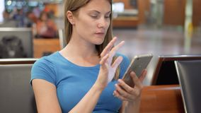 Woman waiting in airport terminal. Using smartphone, browsing, messaging with friends, reading news. Young woman sitting in airport terminal. Waiting for her stock video