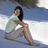 A young woman sitting alone on a beach Stock Photos