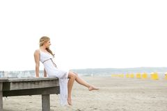 Young woman sitting alone at the beach Royalty Free Stock Photo