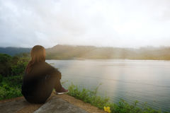 Young woman sitting alone on cliff. front of her have sea and su Stock Photos