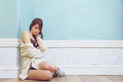 Young woman sitting alone on the floor with sweater Stock Image