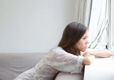 Young woman sitting alone looking out window Royalty Free Stock Image