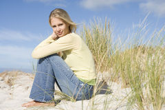 Young woman sitting amongst dunes Royalty Free Stock Image