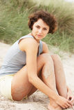 Young Woman Sitting Amongst Sand Dunes Stock Photography