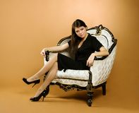 Young woman sitting in armchair. Young beautiful woman sitting in antique armchair Stock Photo