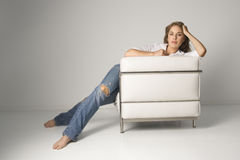 Young Woman Sitting in Armchair Royalty Free Stock Image