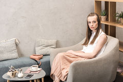 Young woman sitting in armchair drinking coffee and looking at camera Stock Images