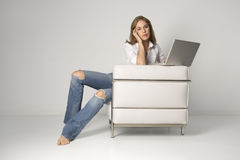 Young Woman Sitting in Armchair With Laptop Royalty Free Stock Photography