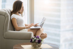 Young woman sitting in armchair with laptop. Young woman in a modern room, comfortable in her armchair with a laptop, operating her business, setting up business Stock Photo