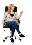 Young woman sitting on armchair pointing right Stock Photography