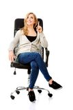 Young woman sitting on armchair pointing up Stock Photography
