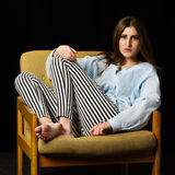 Young woman sitting in the armchair and relaxing Royalty Free Stock Photos