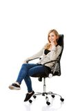 Young woman sitting on armchair touching chin Royalty Free Stock Photo