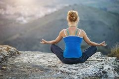 Young woman sitting in asana position on a rock Stock Photo