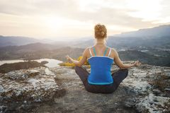 Young woman sitting in asana position on a rock Stock Photos
