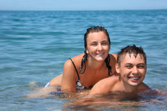 Young woman sitting astride man in sea near coast. Happy young woman sitting astride man in sea near coast Royalty Free Stock Images