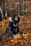 Young woman sitting on autumn forest Stock Photo