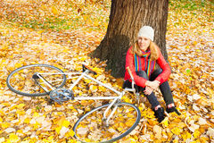 Young woman sitting in autumn leaves. Happy young woman sitting in autumn leaves beside a bicycle stock image