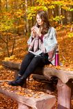 Young woman sitting in autumn outside and drinking from cup. Young brunette woman sitting in autumn outside on bench and drinking from cup Stock Image