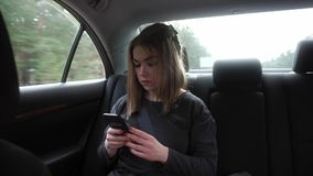 Young woman sitting on the back seat of a car, focused stock video footage