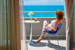 Young woman sitting on the balcony at the see. Rear view of young red haired female relaxing and enjoying sea view on a hotel balcony at a sea resort, Nesebar royalty free stock photos