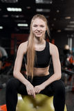 Young woman sitting with a ball in the gym Royalty Free Stock Photo
