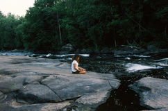 Young Woman Sitting on Bank of Stream Royalty Free Stock Images