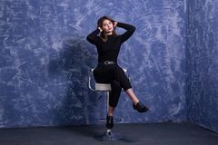 A young woman is sitting on a bar stool against the background of a blue wall, free space. Model posing on a chair portrait pose happy casual looking student stock photos
