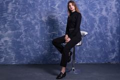 A young woman is sitting on a bar stool against the background of a blue wall, free space. Model posing on a chair portrait pose happy casual looking student stock photography