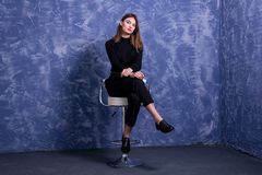 A young woman is sitting on a bar stool against the background of a blue wall, free space. Model posing on a chair portrait pose happy casual looking student stock image