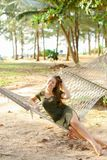 Young woman sitting barefoot on wicker hammock, sand and trees in background. stock image