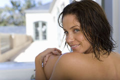 Young woman sitting in bath by window, smiling, portrait Royalty Free Stock Photo