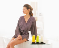 Young woman sitting in bathroom with bath cosmetics stock image